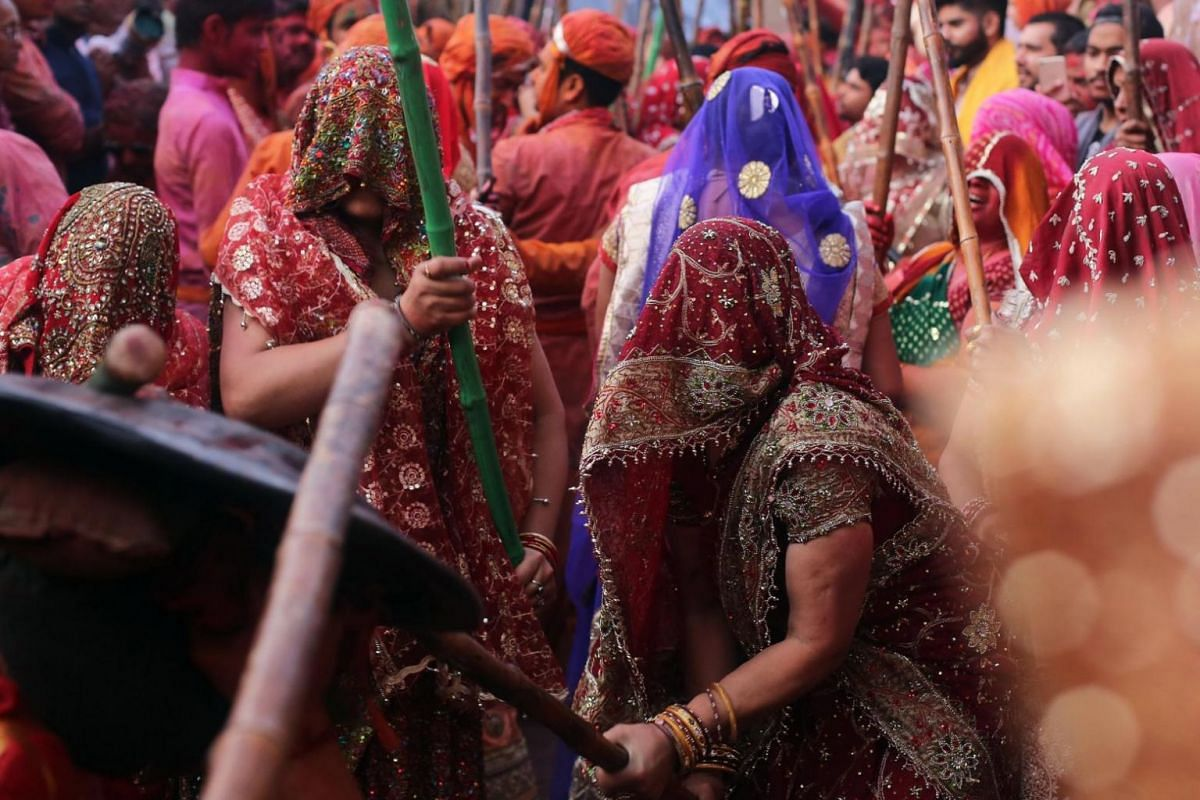 Indian women beating men with sticks during the annual Lathmar Holi festival in Nandgaon, India, on Feb 25, 2018.