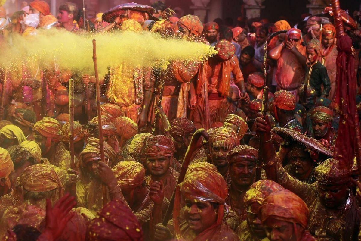Hindu men from the villages of Nandgaon and Barsana covered with colored powder celebrating the Lathmar Holi festival at the Nandgram temple in Nandgaon, India, on Feb 25, 2018.