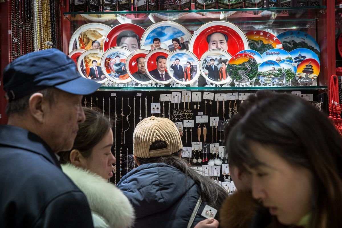 People standing next to souvenir plates with portraits of Chinese President Xi Jinping and former Chinese leader Mao Zedong at a souvenir shop in Beijing, China, on Feb, 26, 2018.