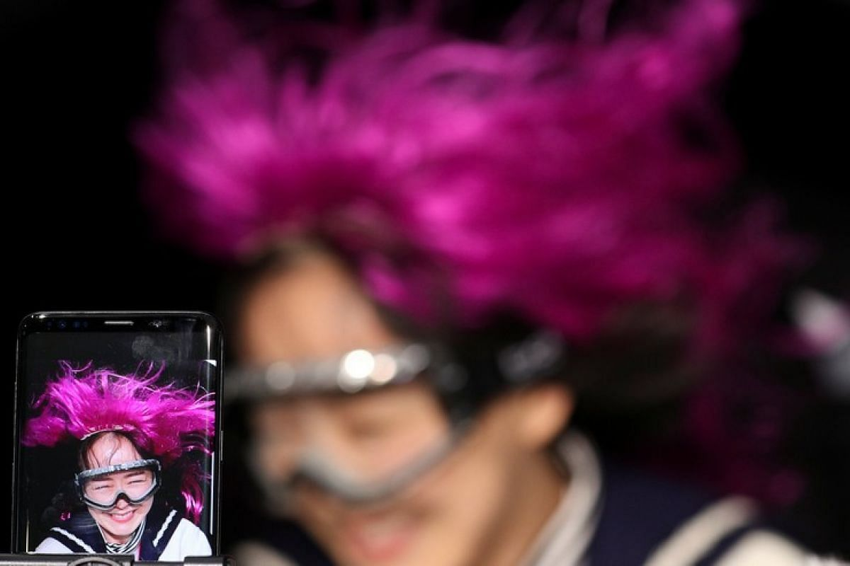 A woman checks Samsung's Galaxy S9+ slow-motion video inside its booth at the Mobile World Congress in Barcelona, Spain on Feb 27, 2018.