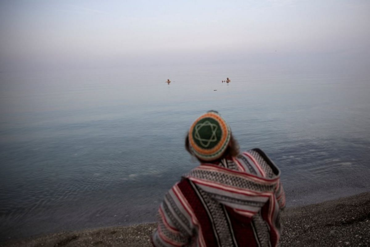 A man sits on the shore of the Dead Sea, near Metzoke Dragot in the Israeli occupied West Bank, on Feb 7, 2018.