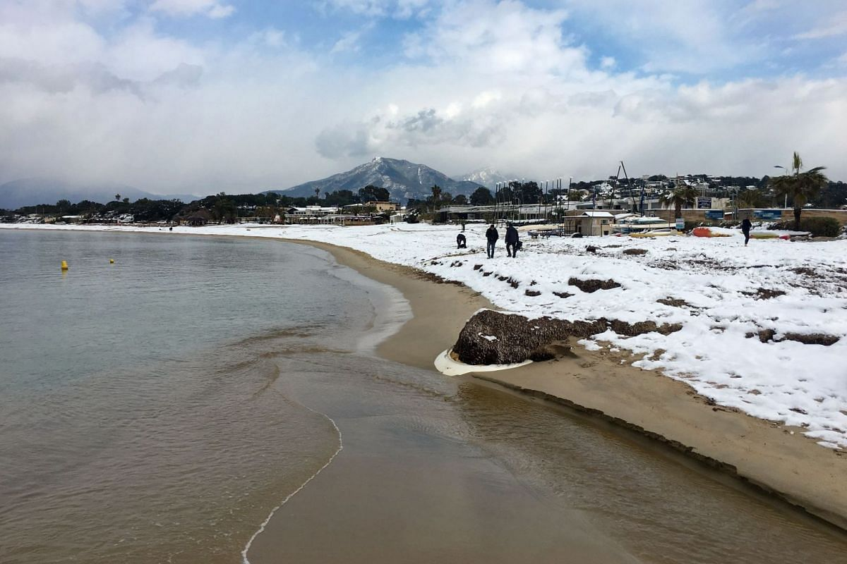 The shore of the bay of Ajaccio is covered with snow, on the French Mediteranean island of Corsica, on Feb 27, 2018. / AFP