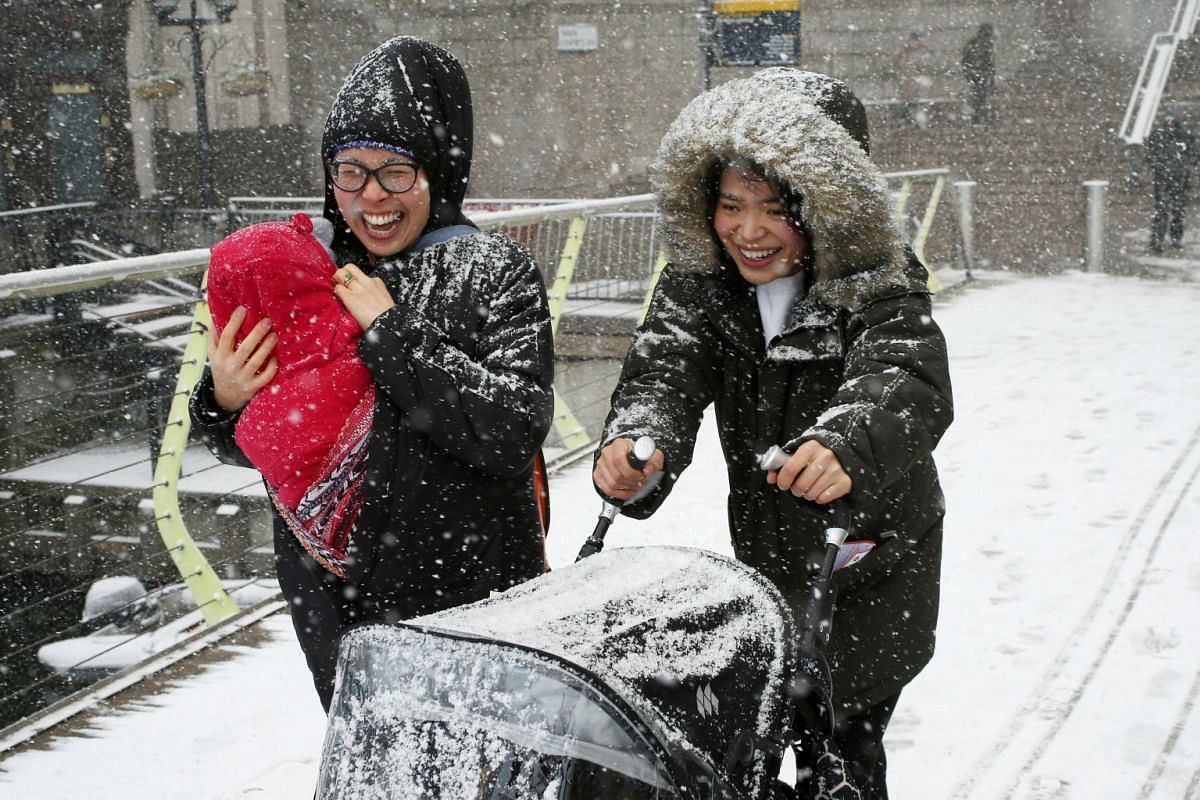 People make their way through the snow in Canary Wharf, London, on Feb 27, 2018.