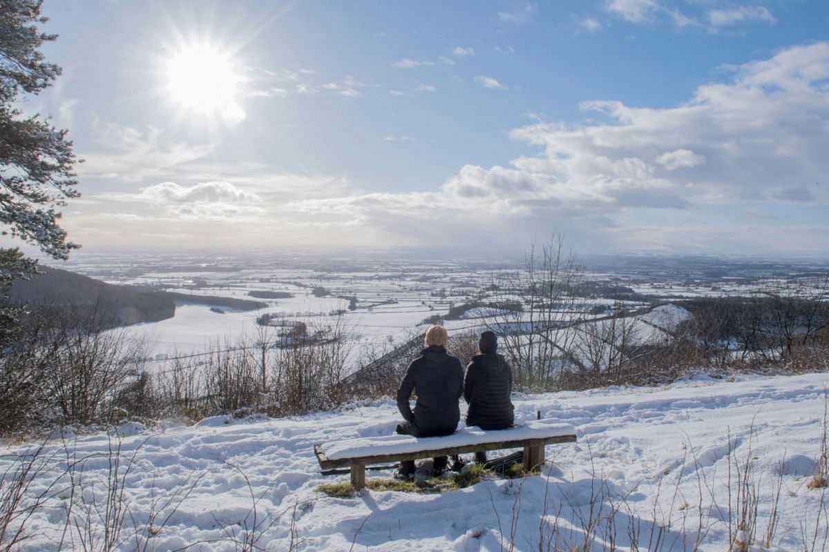 A couple sit on a bench overlooking the snow-covered fields of Thirsk at Sutton bank National Park Centre in the North Yorks Moors National Park in North Yorkshire, on Feb 27, 2018.