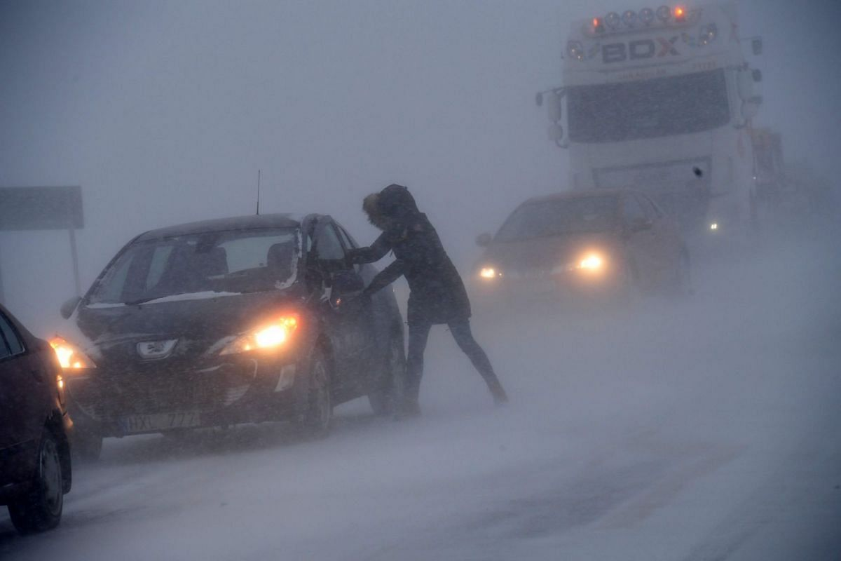 A woman seeks shelter from the blizzard in her stranded car on Feb 27, 2018, near Sjobo, southern Sweden.