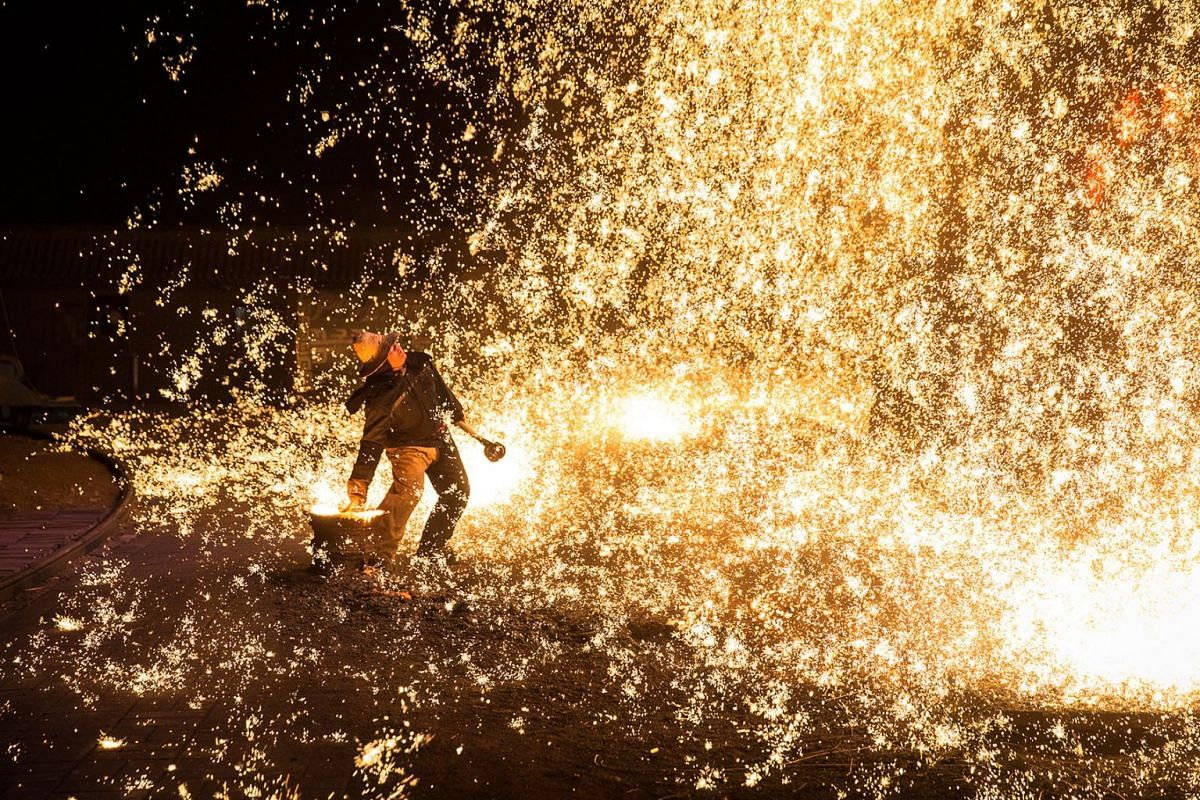 A member of Wang De's Chinese traditional molten iron performance team throws molten iron against a cold stone city wall to create sparks like fireworks, commonly known as 'Da Shu Hua' in Nuanquan Town, rural Zhangjiakou city in Hebei province, China