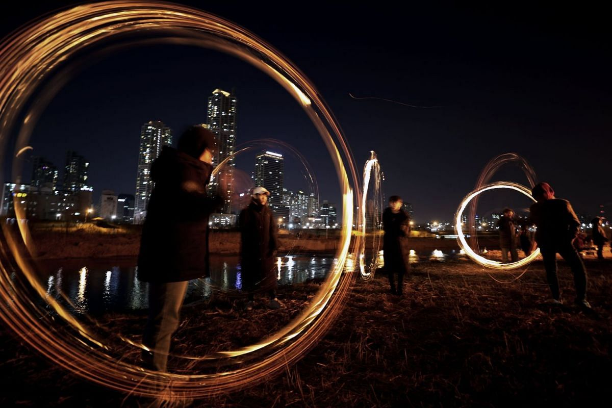 People participate in 'jwibulnori,' a popular game for celebrating the first lunar full moon of the new year, in Seoul, South Korea, Mar 1, 2018. The game, played by twirling burners tied to a long rope, is usually held in rice paddies to chase away