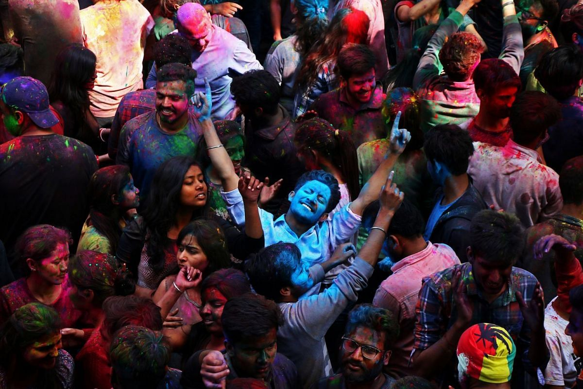 Students with their faces smeared in coloured powder dance as they celebrate Holi at a university campus in Chandigarh, India on Mar 1, 2018. Photo: REUTERS