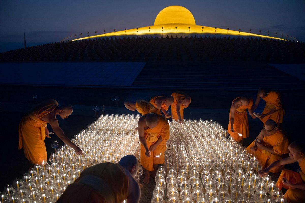 Buddhist monks light candles during evening prayers to mark Makha Bucha Day at Wat Phra Dhammakaya temple, near Bangkok on March 1, 2018. Makha Bucha Day is held in celebration of the teachings of the Lord Buddha on the full moon of the 3rd lunar mo
