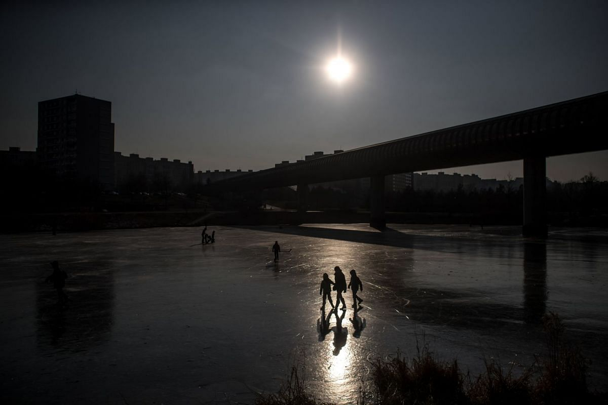 People enjoy a cold afternoon on a frozen pond in Prague, Czech Republic, on March 1, 2018.
