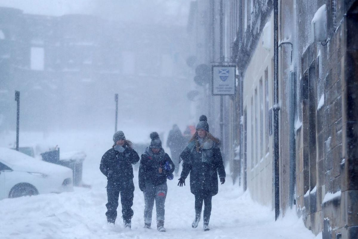 People walk along the street through the snow near Sterling Castle, Scotland, Britain, on March 1, 2018.