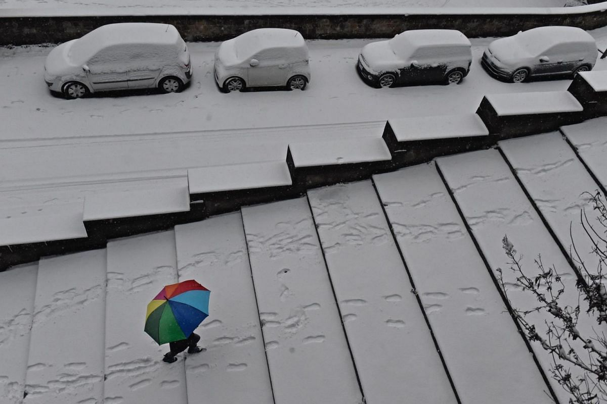 A person using an umbrella walks along a path as snow falls in Florence, Italy, on March 1, 2018.