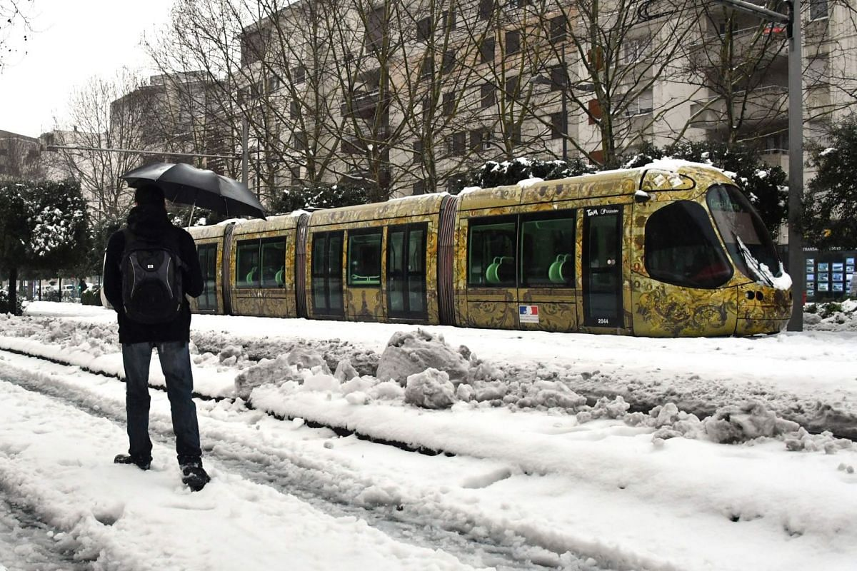 A man walks on a snow covered road past a tramway blocked by snow on March 1, 2018 in Montpellier, southern France, after heavy snow fall.