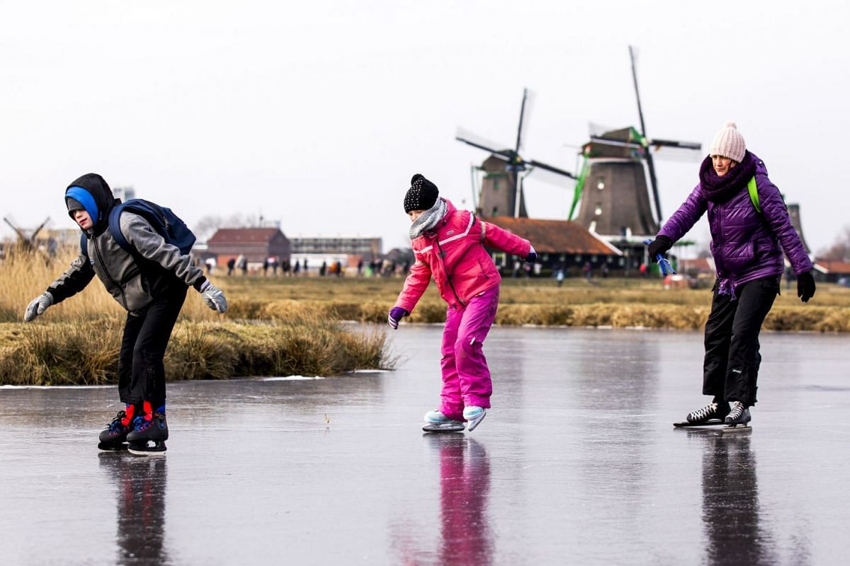 Ice skaters skate on natural ice at the Dutch 'Zaanse Schans' near Zaandam on March 1, 2018.