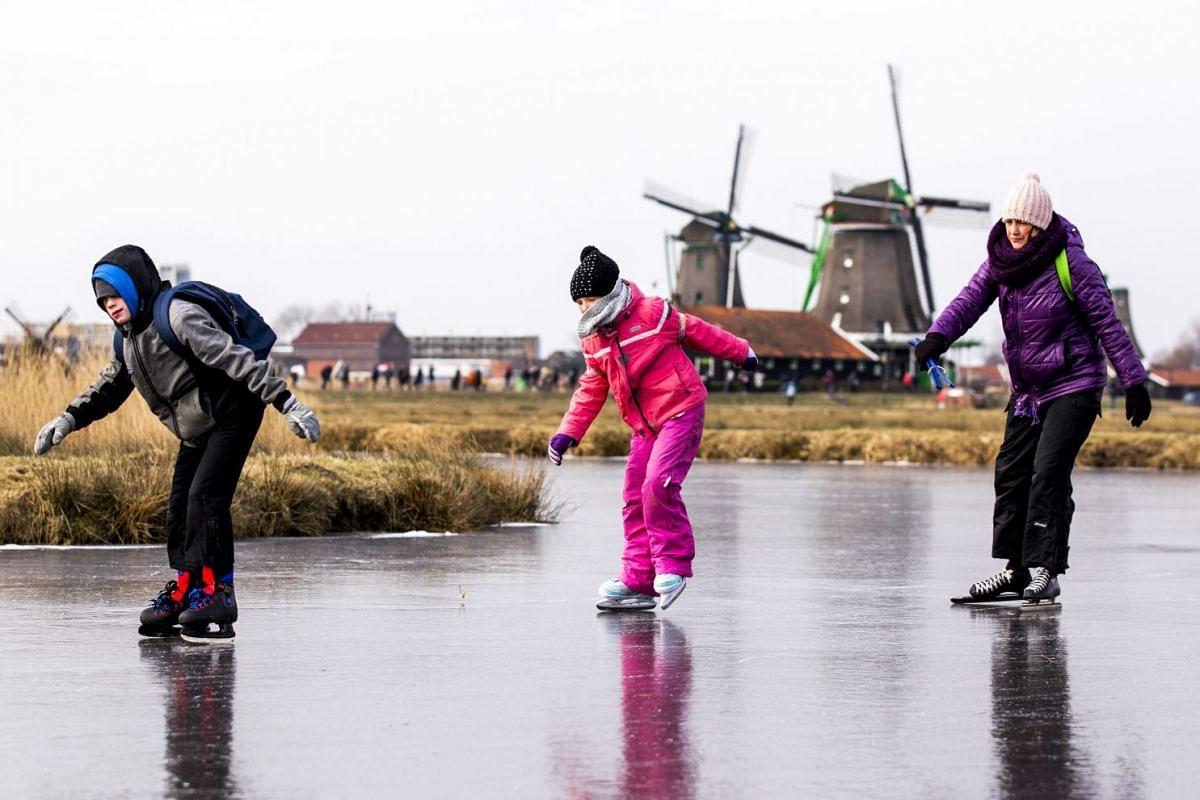 Ice skaters skate on natural ice at the Dutch 'Zaanse Schans' near Zaandam on March 1, 2018.