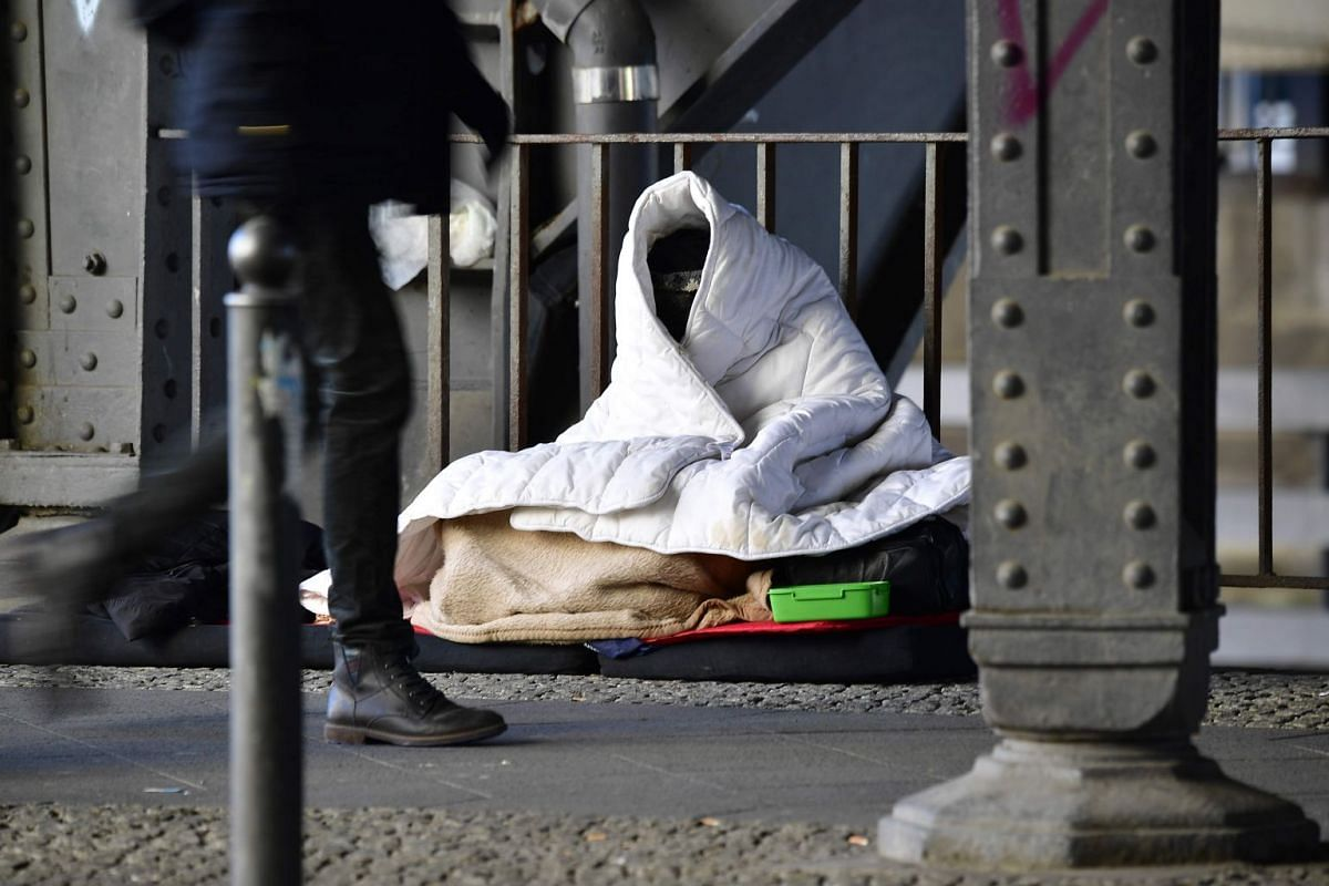 A man protects himself from the cold with blankets in Berlin's Mitte central district on March 1, 2018.
