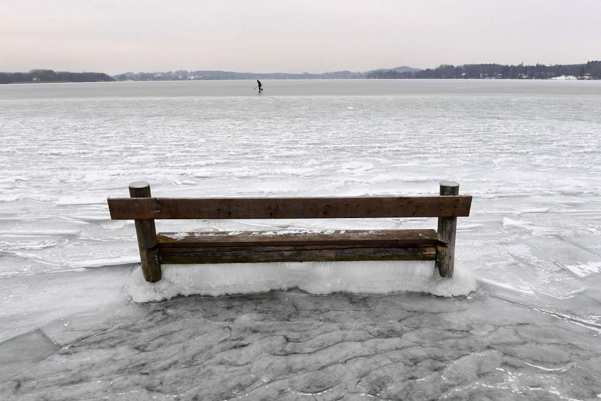 A woman ice skates behind a bench caught in the ice on the frozen Woerthsee lake on March 1, 2018 near the Bavarian village of Inning, southern Germany, as temperatures fell under minus eight degrees celsius.