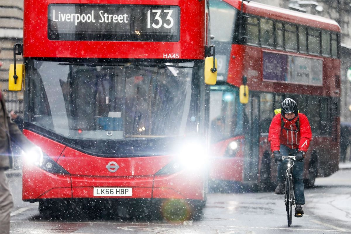 A cyclist rides past buses in the snow during the morning rush hour in London, on Thursday, March 1, 2018.