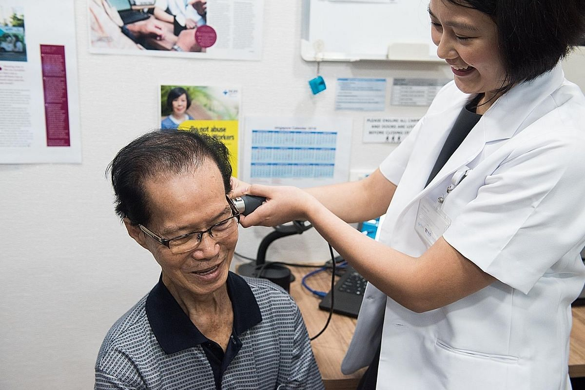 Retiree Lim Koh Beng, who has hearing loss, gets his ears checked by an audiologist at the National University Hospital's Mobile Hearing Clinic.
