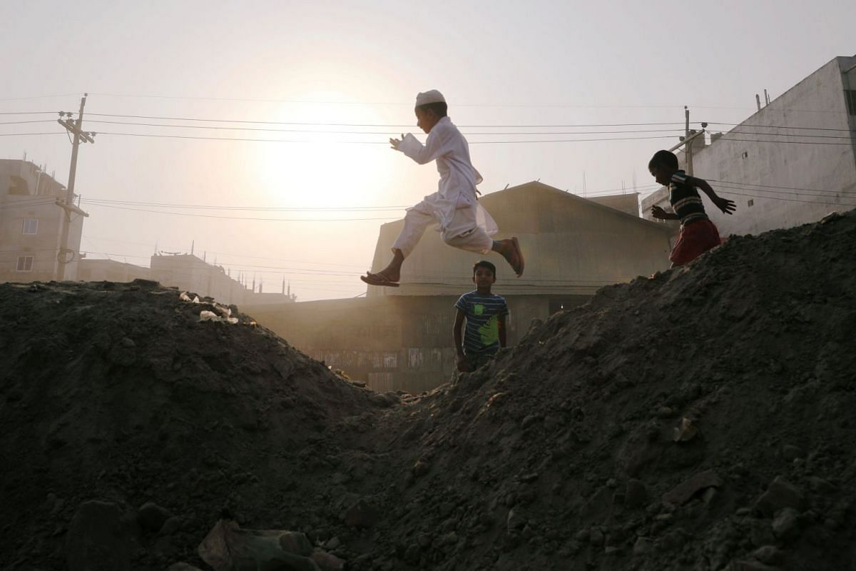 A boy jumps between stacks of sand as he plays in Dhaka, Bangladesh March 4, 2018. PHOTO: REUTERS