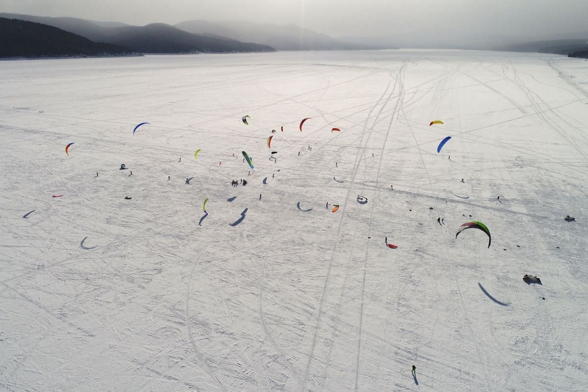 Kite boarders and kite skiers compete during a regional snow kiting championship on the ice-covered Yenisei River outside Krasnoyarsk, Russia March 4, 2018. PHOTO: REUTERS
