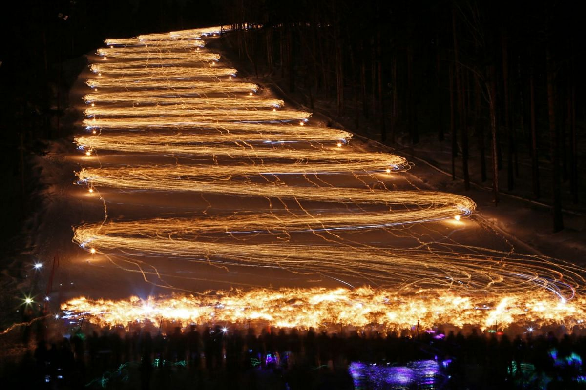 Hundreds of skiers and snowboarders hold lit torches and flashlights while descending from a slope during an annual festival in the Siberian town of Zheleznogorsk near Krasnoyarsk, Russia March 3, 2018. PHOTO: REUTERS