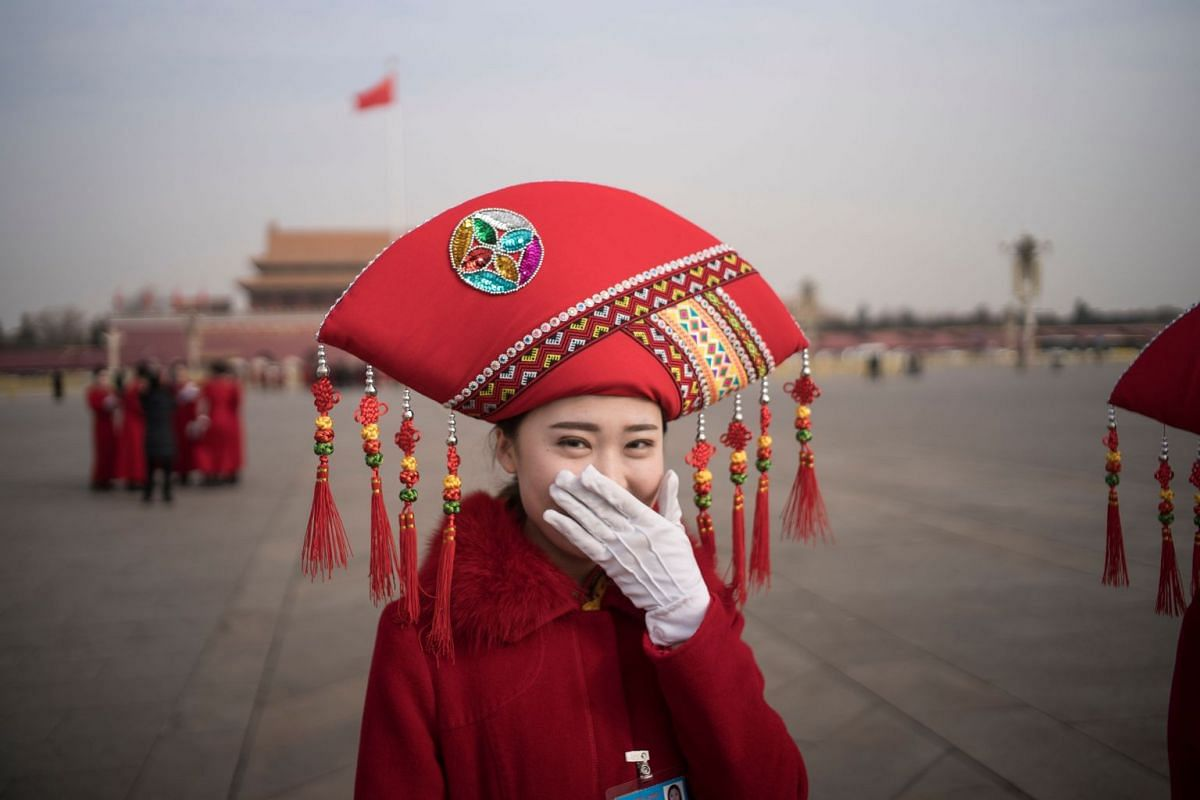 A Chinese hostess reacts at Tiananmen square during the opening session of the National People's Congress, China's legislature, in Beijing on March 5, 2018. PHOTO: AFP