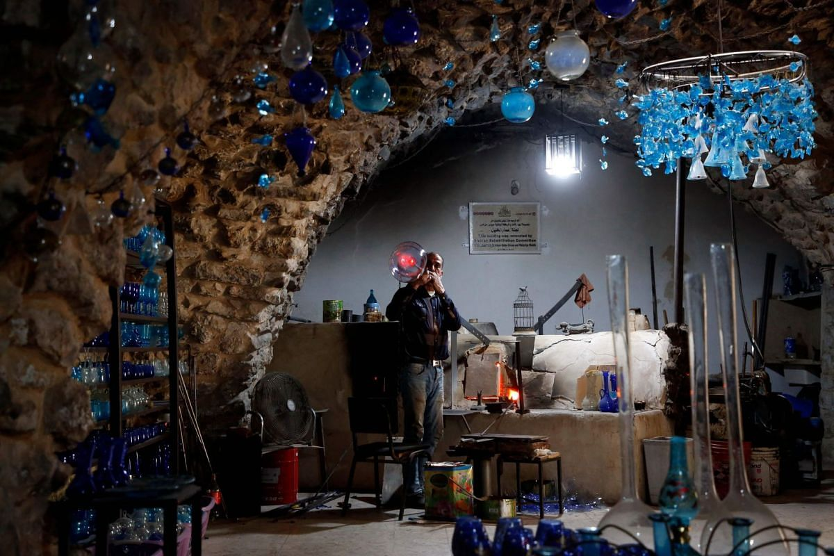Yaacqoub al-Natsheh, a professional glassblower who has been forming glass for over 40 years, works at his new workshop near the Ibrahimi Mosque, in the divided West Bank town of Hebron on March 4, 2018. PHOTO: AFP