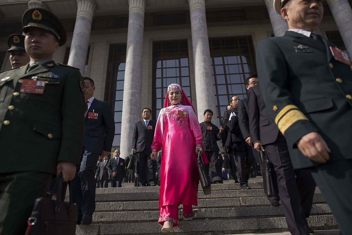 A delegate (centre), wearing an ethnic minority outfit, and military delegates (left and right) leave the Great Hall of the People after the opening session of the National People's Congress in Beijing on March 5, 2018.