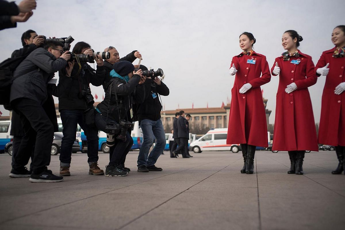 Photographers take pictures of Chinese hostesses in Tiananmen square during the opening session of the National People's Congress in Beijing on March 5, 2018.