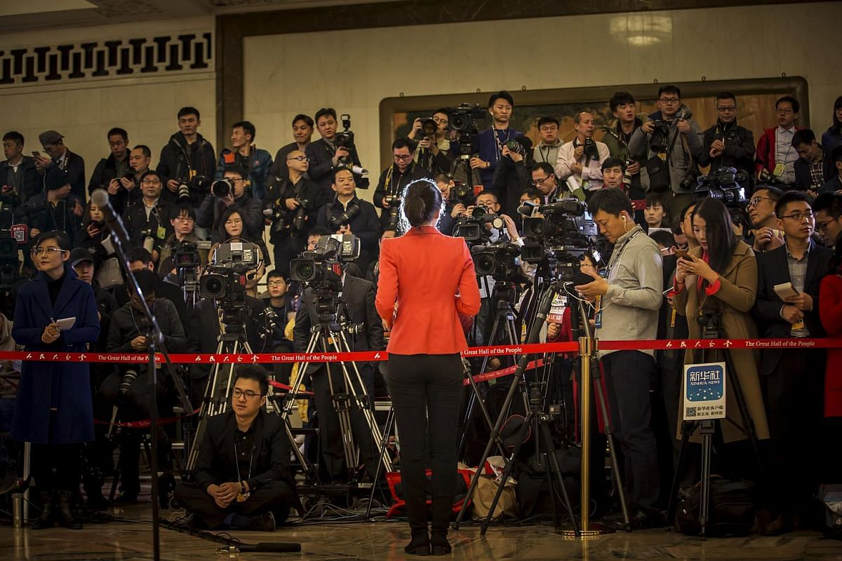 A reporter stands in front of members of the media inside the Great Hall of the People ahead of the opening of the first session of the 13th National People's Congress (NPC) in Beijing on March 5, 2018.