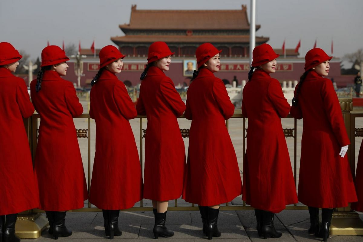 Chinese stewardesses pose for photos on Tiananmen Square before the opening of the first session of the 13th National People's Congress (NPC) at the Great Hall of the People in Beijing on March 5, 2018.