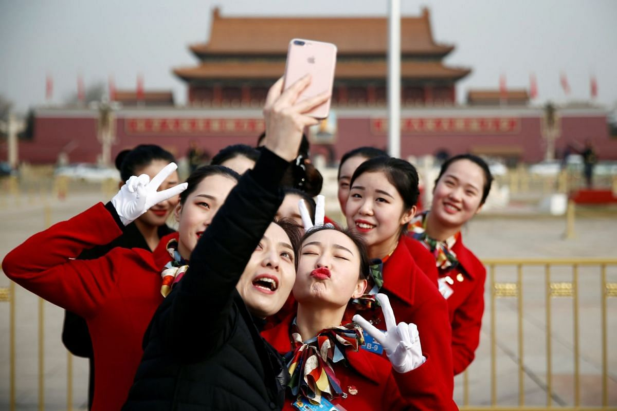 Ushers pose for pictures at the Tiananmen Square during the opening session of the National People's Congress (NPC) in Beijing on March 5, 2018.