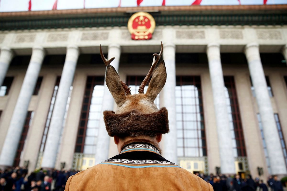 A delegate in traditional costume arrives for the opening session of the National People's Congress (NPC) at the Great Hall of the People in Beijing on March 5, 2018.