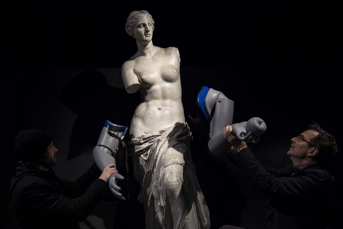 Xavier Ducrest (R), director France of Handicap International helps to symbolicly attach prosthetic arms to a replica of the Venus de Milo is displayed with during an action led by Handicap International to raise awareness on the thousands of amputee