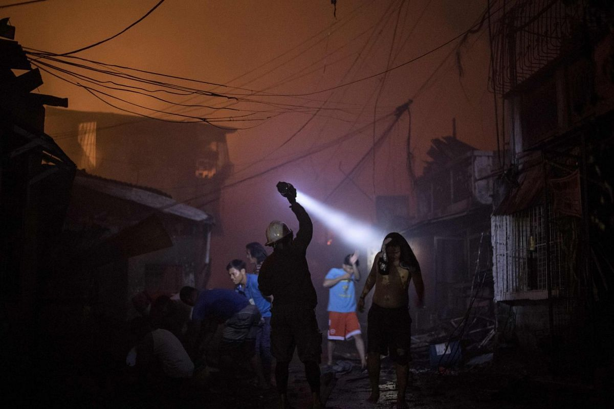 A fireman uses his flashlight during a huge fire that engulfed a slum area in Manila on March 7, 2018. PHOTO: AFP