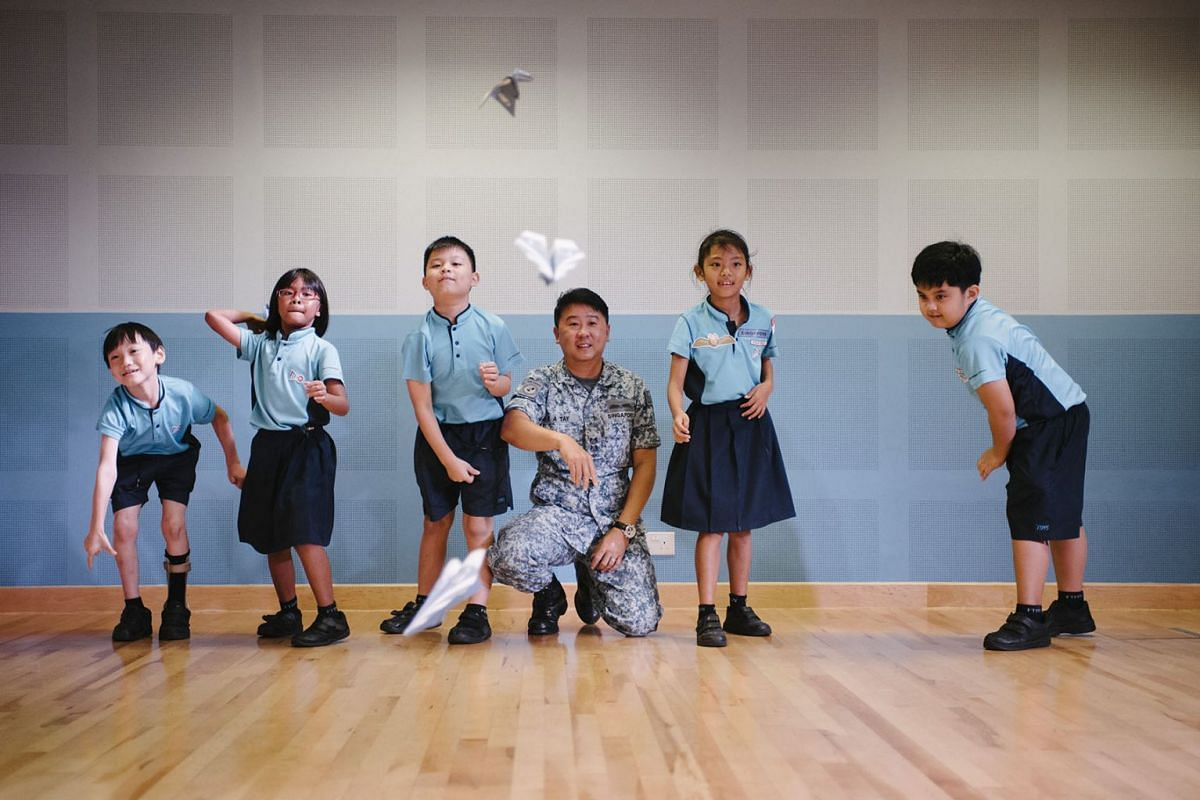 Lieutenant-Colonel Tay Kok Ann, 45, head of the Experience and Engagement Group for RSAF50@Heartlands, throwing paper planes with Primary 2 pupils from First Toa Payoh Primary School on March 5, 2018 during an engagement activity to celebrate the Rep