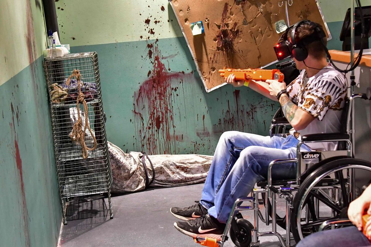Gamers wearing virtual reality (VR) goggles play with plastic shotguns while sitting in wheelchairs at a newly-opened VR park at The Dubai Mall on March 6, 2018. PHOTO: AFP