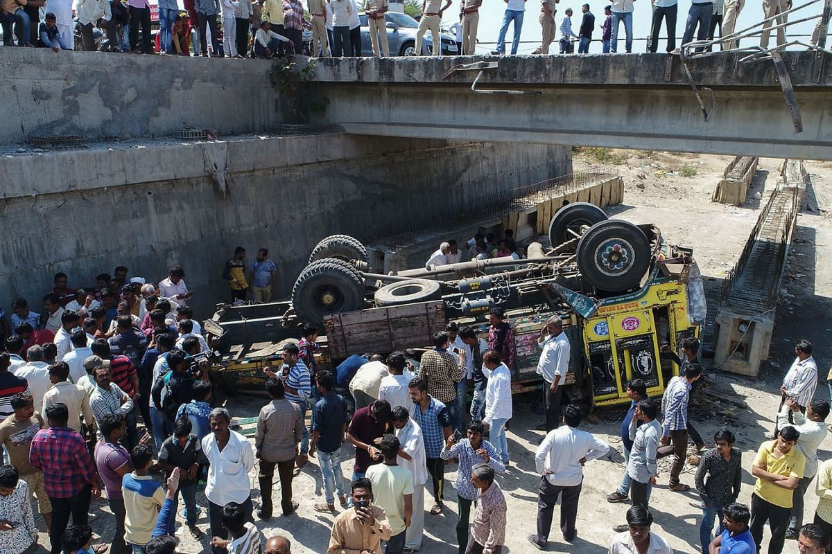 Onlookers gather around the debris of a truck that plunged off a bridge in Bhavnagar district, about 200km from Ahmedabad in India's western Gujarat state, killing at least 25 people on March 6, 2018. PHOTO: AFP