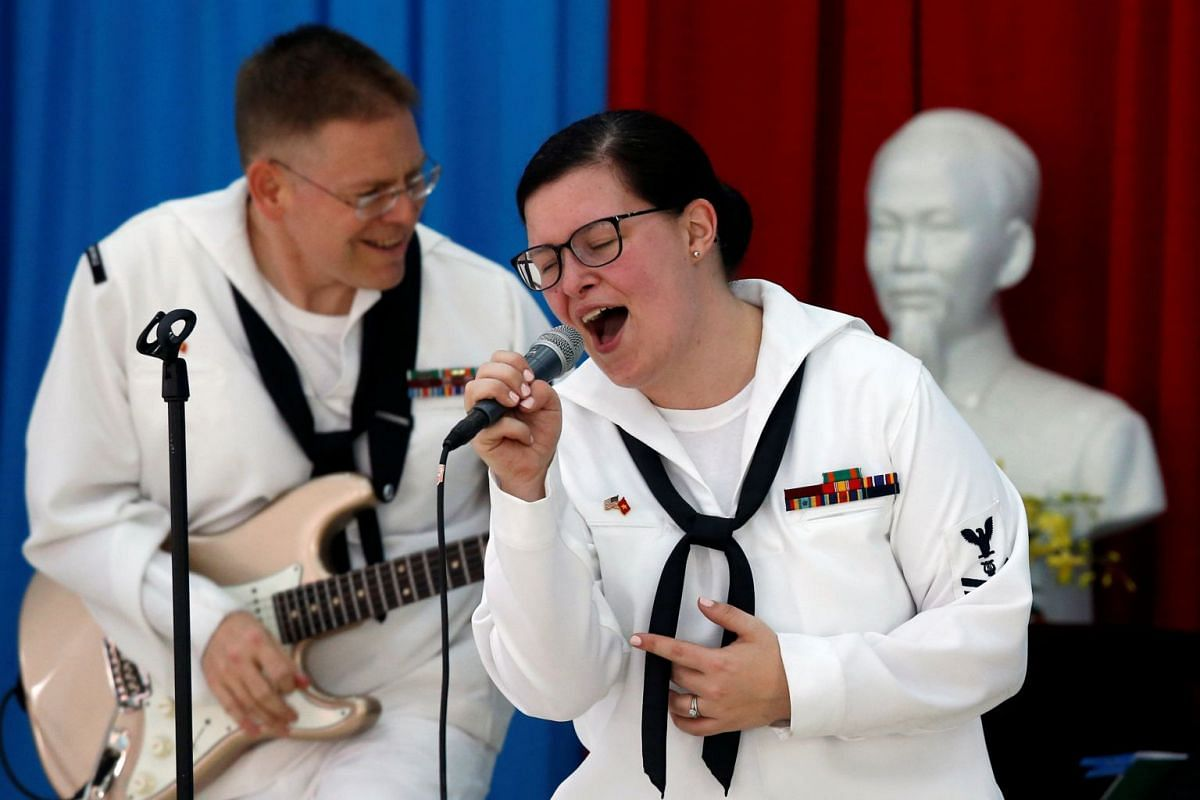 Members of US Seventh Fleet Band perform as a statue of late Vietnamese revolutionary leader Ho Chi Minh is seen in the background, at the Da Nang SOS Children's Village as part of the visit to Vietnam of US aircraft carrier Carl Vinson, on March 6,