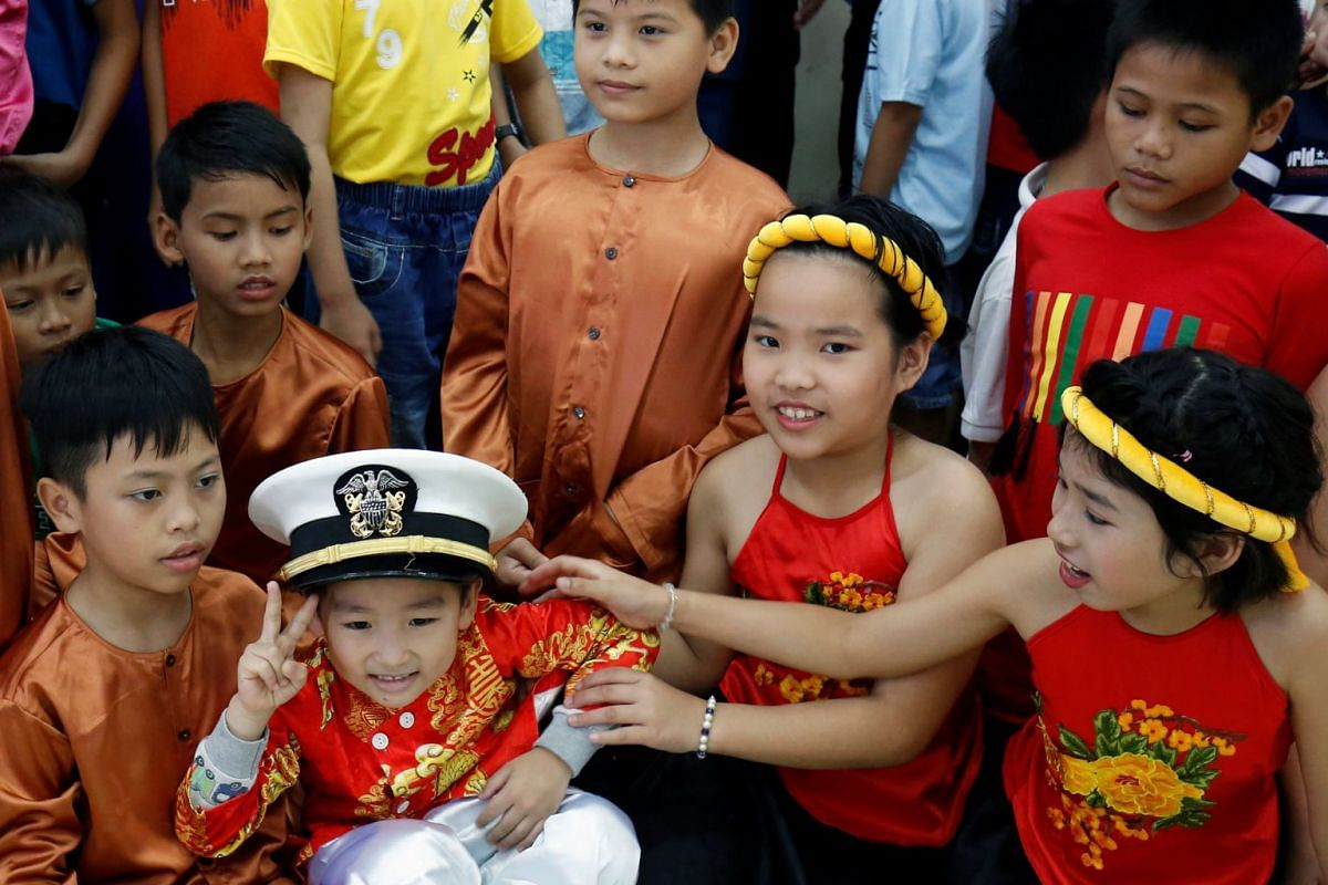 A child wears a US Navy hat during a visit of sailors to Da Nang SOS Children's Village as part of the visit to Vietnam of US aircraft carrier Carl Vinson, on March 6, 2018.