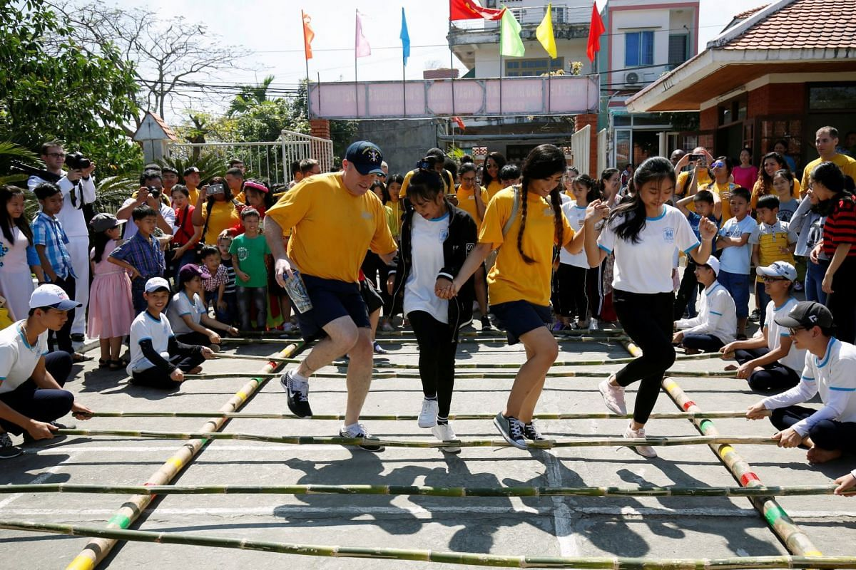 US sailors (yellow shirts) dance with children at the Da Nang SOS Children's Village as part of the visit to Vietnam of US aircraft carrier Carl Vinson, in Danang, Vietnam, on March 6, 2018.