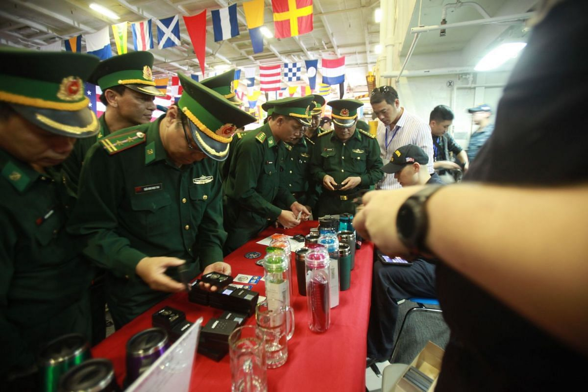 Vietnamese military officers purchase souvenirs while touring the USS Carl Vinson (CVN-70), anchored off the coast in Danang, on March 5, 2018.