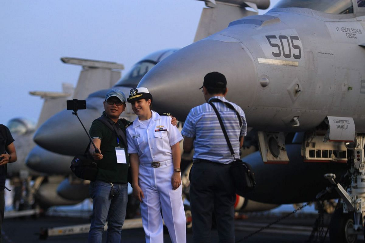 A US Navy officer poses for a photograph with a Vietnamese photographer aboard the USS Carl Vinson (CVN-70), anchored off the coast in Danang, on March 5, 2018.