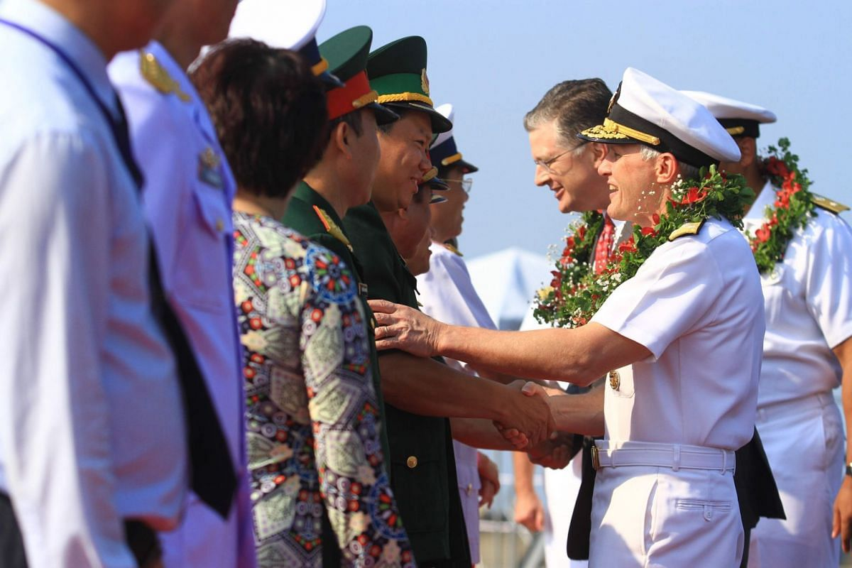 Vice-Admiral Phillip G. Sawyer (right), Commander of the US Navy's 7th Fleet, greets Vietnamese officials after the US aircraft carrier USS Carl Vinson pulled into port in Danang, on March 5, 2018.
