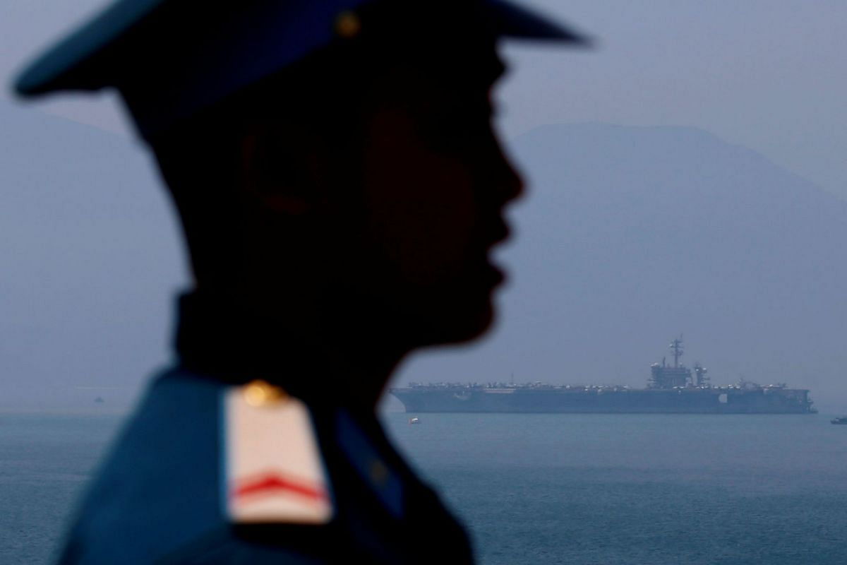 A Vietnamese soldier keeps watch in front of US aircraft carrier USS Carl Vinson after its arrival at a port in Danang, Vietnam, on March 5, 2018.