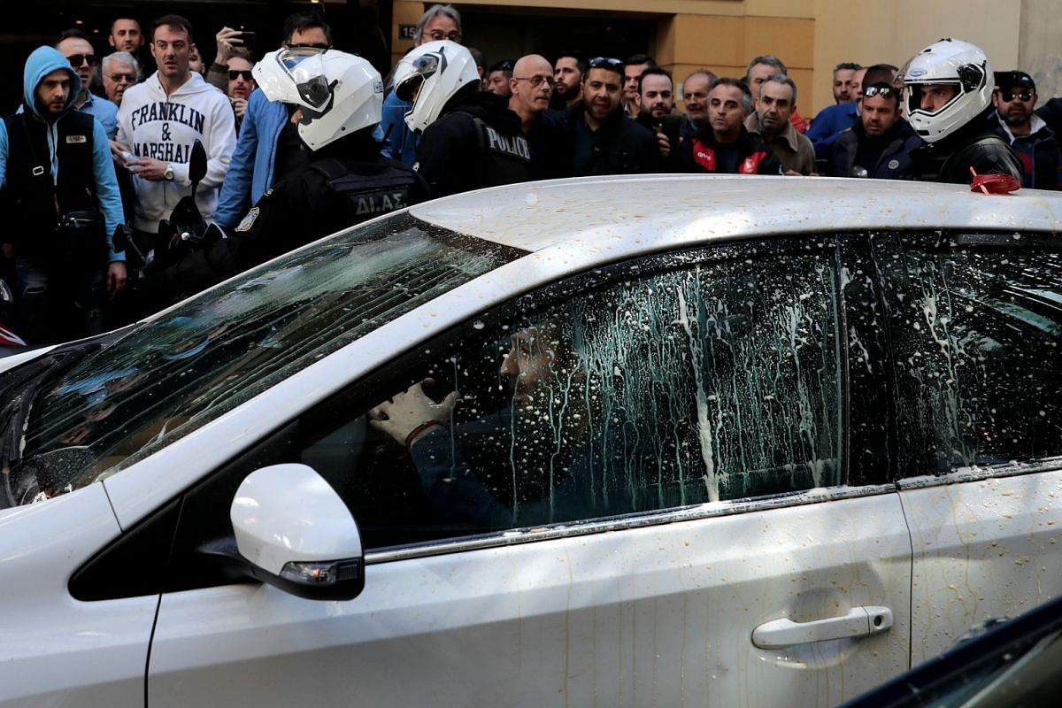 Greek taxi drivers surround a vehicle they say is being used by an Uber driver during a protest against taxi-hailing apps such as Uber in Athens, Greece March 6, 2018. PHOTO: REUTERS