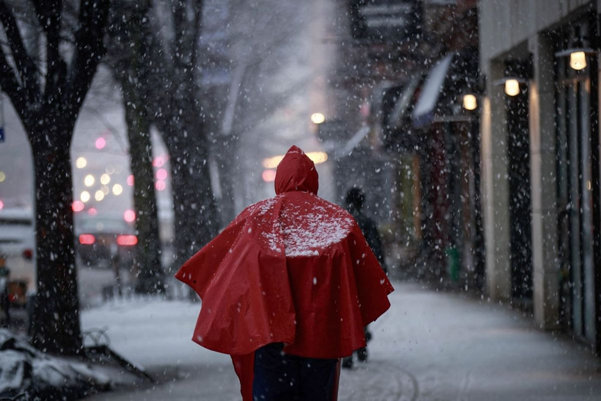 A man wears a red poncho as he walks along Atlantic Avenue in Brooklyn during a snowstorm, March 7, 2018 in New York City. PHOTO: GETTY IMAGES/AFP