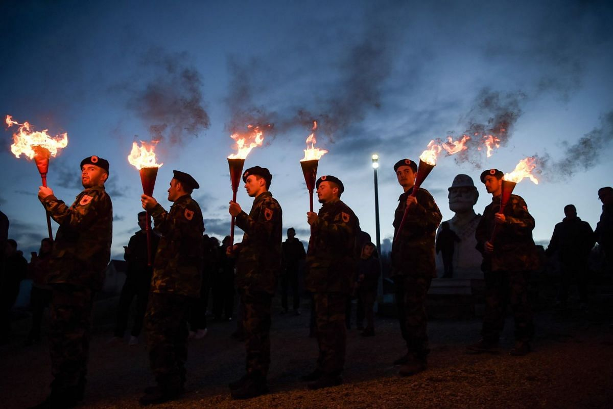 Kosovo Albanians dressed in military costumes carry torches during a bonfire ceremony marking the 20th anniversary of the killing of Kosovo Liberation Army (KLA) founding member and commander Adem Jashari, whose sculpture is seen rear, on March 7, 20