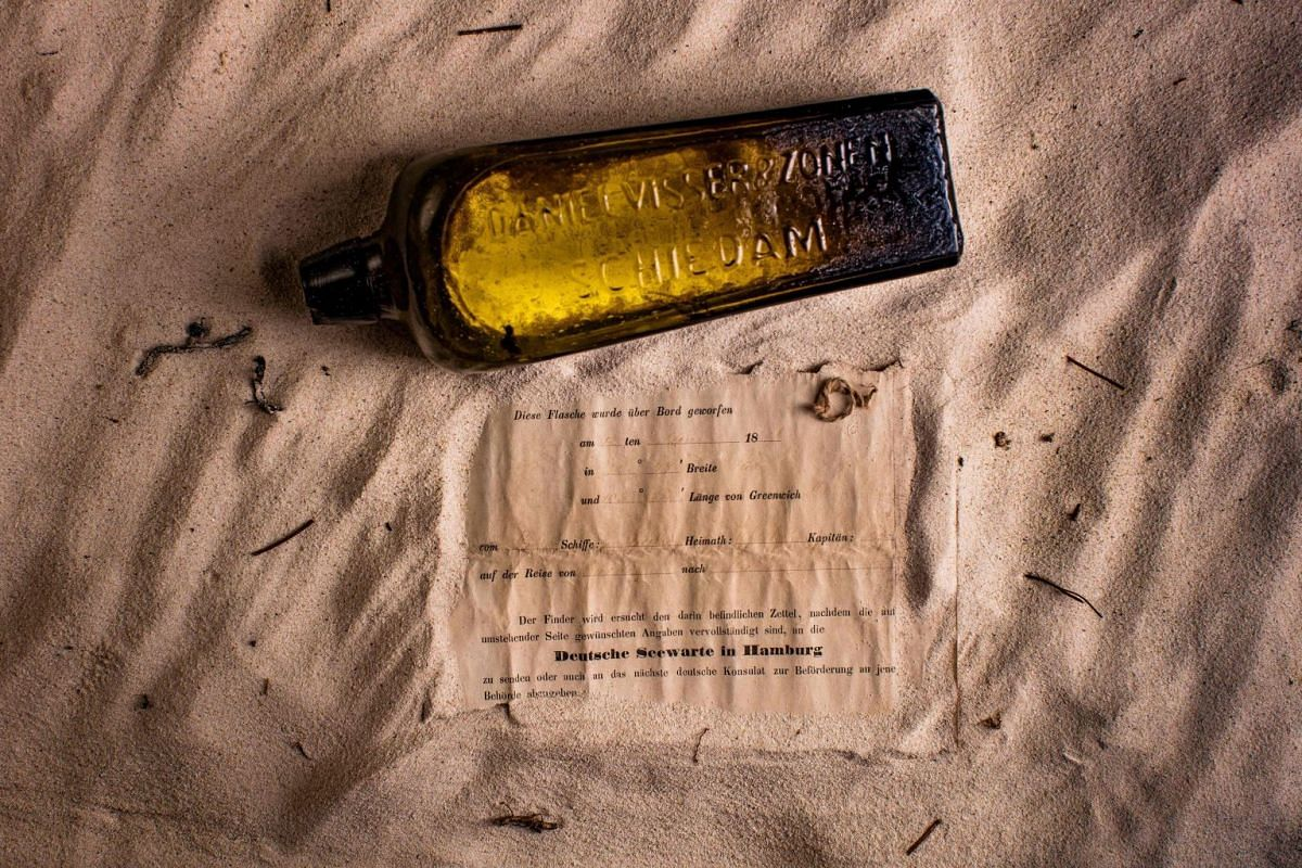 This undated photo received courtesy from Kym Illman on March 7, 2018 shows a bottle and the almost 132-year-old message it contained, that was found near Wedge Island, some 160 kilometres (99 miles) north of Perth. PHOTO: KYM ILLMAN VIA AFP